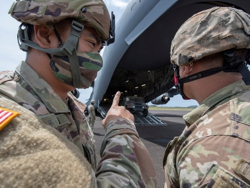 Spc. Donoven Lau and Spc. Kalani Scanlan Jr. discuss humvee driving safety as they wait for the vehicles they would operate as they were being offloaded from a C-17 Globemaster III at Lihue Airport, Apr. 23, 2020. (Senior Airman Orlando Corpuz/Air Force)