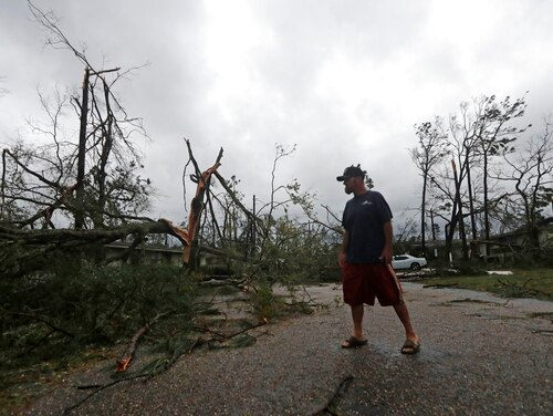 James Prescott surveys the damage as the remnants of Hurricane Michael move through Panama City, Fla., on Wednesday. He was visiting a friend and was not able to leave the street due to downed trees. Tyndall Air Force Base near Panama City said it had sustained a direct hit from the catastrophic storm, causing extensive damage, and that it did not know when personnel will return. (Gerald Herbert/AP)