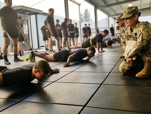 Sgt. 1st Class Kimberlee Hilliard, an Army Reserve soldier and master fitness trainer with the Army Physical Fitness School, observes for proper form as soldiers assigned to 2nd Battalion, 75th Ranger Regiment at Joint Base Lewis-McChord, Washington perform T pushups. The pushups measure upper body muscular endurance. (Stephanie Slater/Army)