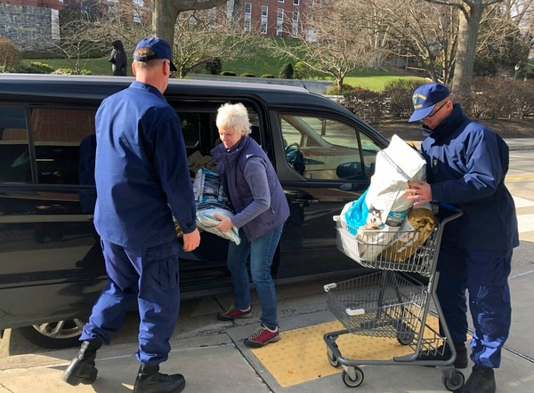 Christine Lamb, president and founder of the nonprofit group Animal House Inc., in nearby Waterford, Conn., delivers bags of donated pet food to Coast Guardsmen helping at a pop-up food pantry created on the grounds of the U.S. Coast Guard Academy in New London, Conn. (Susan Haigh/AP)