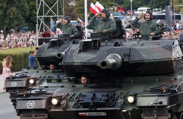 Polish Army soldiers salute as tanks roll on one of the city's main streets during a yearly military parade celebrating the Polish Army Day in Warsaw, Poland, Wednesday, Aug. 15, 2018. Poland marks Army Day with a parade and a call for US permanent military base in Poland. (AP Photo/Czarek Sokolowski)
