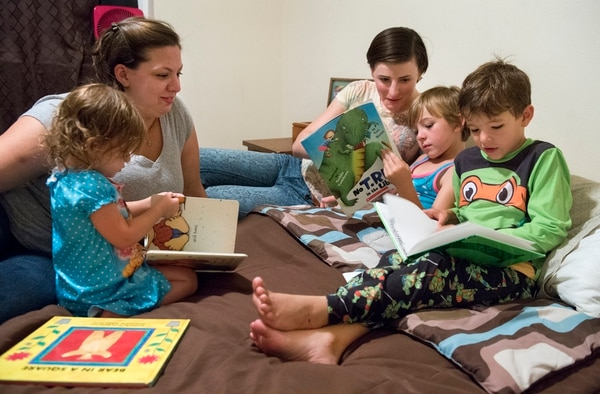 In this photo taken on Aug. 28, 2015, Jennifer Peace, right, and her spouse, Deborah, read books with their children before putting them to bed at their home in Spanaway, Wash. Peace is one of an estimated 15,000 transgender people who serve in the active-duty military. She's speaking out in the hopes of helping people understand transgender men and women.