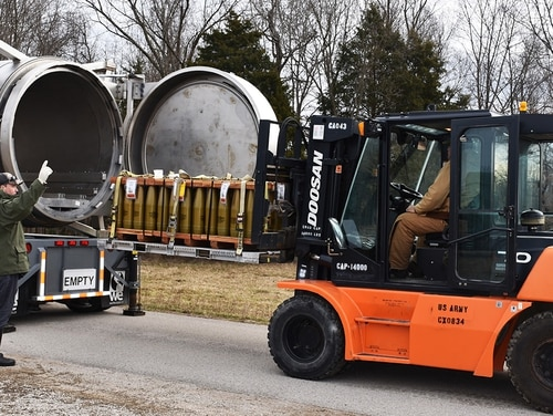 Jonathan Strunk, left, and James Nunn, both Blue Grass Chemical Activity toxic materials handlers, work together to guide training munitions into an enhanced on-site container during munitions movement training in the chemical limited area at the Blue Grass Army Depot on Feb. 13, 2019. (Angela Messinger/Army)