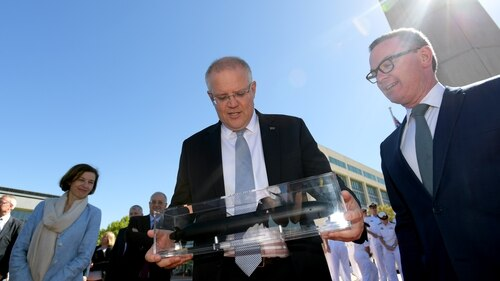Australian Prime Minister Scott Morrison, center, with a model of a submarine after signing a Strategic Partnership Agreement with France at Sir Thomas Blamey Square on Feb. 11, 2019, in Canberra, Australia. (Photo by Tracey Nearmy/Getty Images)