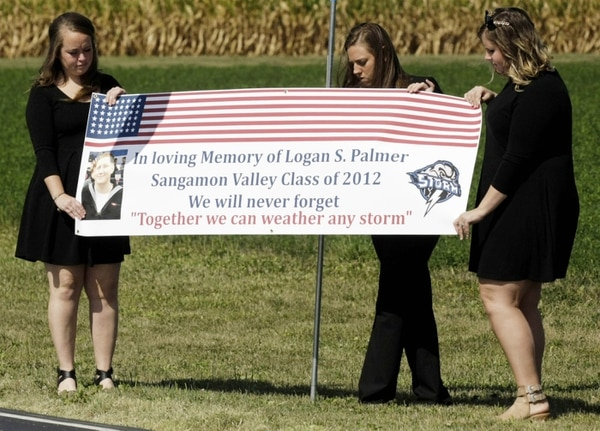 From left: Hunter Hill, Saria Lappin and Heather Albert display a sign of support for those participating in the funeral procession for Logan S. Palmer at Life Foursquare Church in Decatur, Ill., Monday, Sept. 11, 2017. Palmer was one of several sailors who died when the USS McCain collided with an oil tanker near Singapore last month. The three women were in the same graduating class as Palmer at Sangamon Valley High School. (Jim Bowling/Herald & Review via AP)