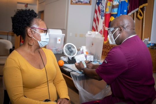 DoD has eased requirements for Tricare Prime enrollees to be able to get the COVID vaccine. Here, Carlton Chase, licensed vocational nurse, prepares to administer the COVID-19 vaccine to Wanda Elaine Brown, medical clerk, at Brooke Army Medical Center, Fort Sam Houston, Texas, Jan. 26. (Jason W. Edwards/Army)