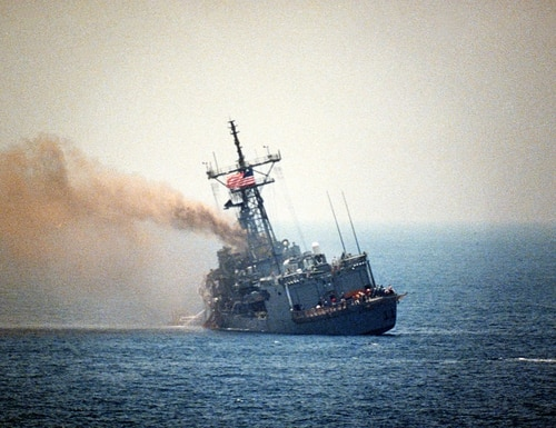The guided missile frigate Stark lists to port after being struck by an Iraqi-launched missile. (WikiMedia)
