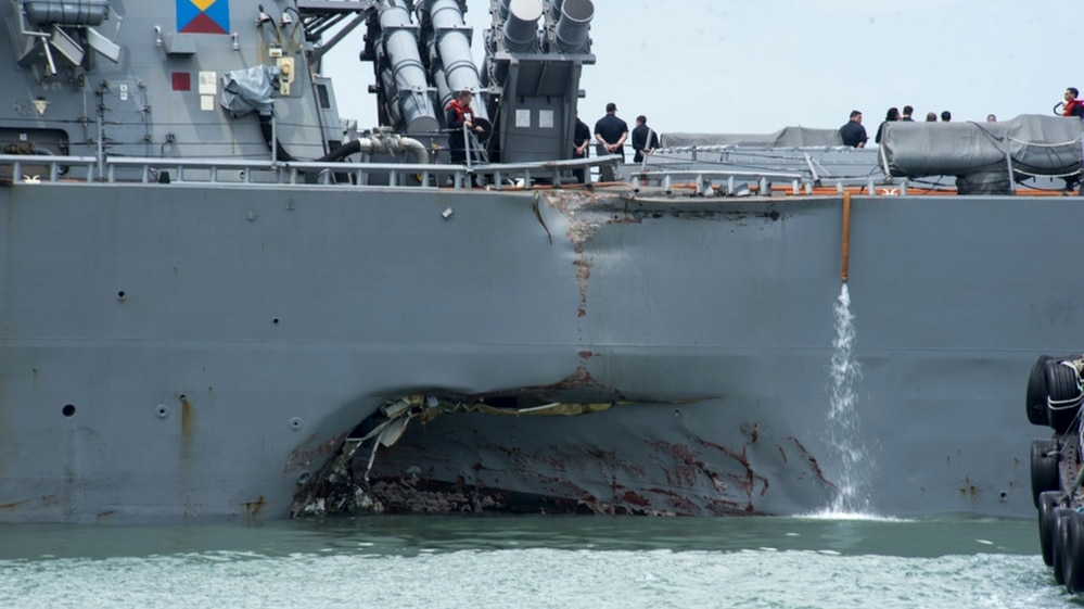 Damage to the portside is visible as the Guided-missile destroyer USS John S. McCain (DDG 56) steers towards Changi naval base in Singapore following a collision with the merchant vessel Alnic MC Monday, Aug. 21, 2017. (MC2 Joshua Fulton/U.S. Navy via AP)