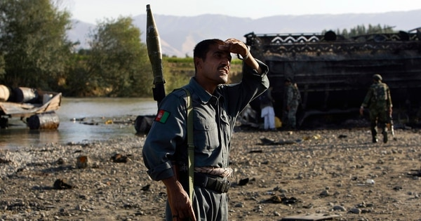 Afghan police inspect the site where villagers died in September 2009 when a U.S. F-15E bombed fuel tankers hijacked by the Taliban. (Anja Niedringhaus/AP)