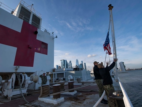 Sailors participate in a morning colors ceremony April 1, 2020, aboard the hospital ship USNS Comfort (T-AH 20) while moored in New York City in support of the nation's COVID-19 response efforts. (Mass Communication Specialist 2nd Class Sara Eshleman/Navy)