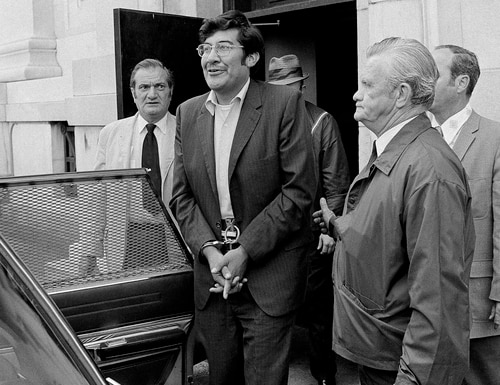 In this Aug. 30, 1972, file photo, Guillermo Aillon, center, emerges from the Superior Court House where he was denied bail on charges he murdered his estranged wife and her parents in New Haven, Conn. (Bob Child/AP)