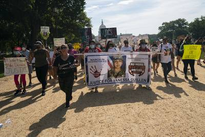 Supporters of the family of slain Army Spc. Vanessa Guillen march to the White House along the National Mall as Capitol Hill is seen in the distance after a news conference, Thursday, July 30, 2020, in Washington.