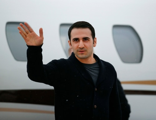 In this Jan. 21, 2016, file photo, Amir Hekmati waves after arriving on a private flight at Bishop International Airport in Flint, Mich. (Paul Sancya/AP)