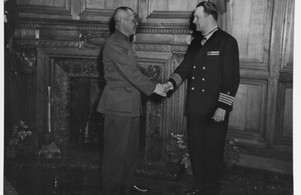 Capt. Irwin F. Beyerly is congratulated by Gen. Chien Ta-Chun, Mayor of Shanghai, after presentation of a medal on behalf of Generalissimo Chiang Kai-Shek for the meritorious part he played in the Sino-American Cooperative Organization (SACO), Feb. 21, 1946. (National Archives)