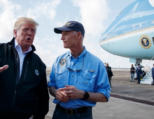 Florida Gov. Rick Scott, right, looks on as President Donald Trump talks with reporters after arriving at Eglin Air Force Base to visit areas affected by Hurricane Michael, Monday. (Evan Vucci/AP)