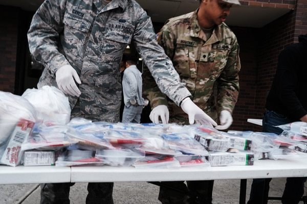 """Members of the New York National Guard hand out bags of food to residents near a 1-mile radius """"containment area"""" set up to halt the coronavirus COVID-19 on March 12, 2020, in New Rochelle, N.Y. (Spencer Platt/Getty Images)"""