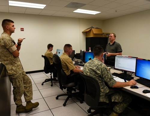 161021-N-FI568-124 PENSACOLA, Fla. (Oct. 21, 2016) Marine Sgt. Jeremy Scott asks a question to Brion Lang, an instructor for the Joint Cyber Analysis Course (JCAC), during an independent study session at Information Warfare Training Command Corry Station. JCAC trains enlisted personnel from all services in the skills and knowledge to perform technical network analysis in cyberspace operations. (U.S. Navy photo by Petty Officer 3rd Class Taylor L. Jackson/Released)