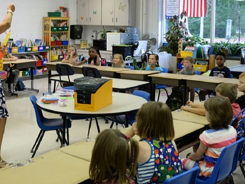 A proposal would fund education savings accounts for military families with money now used to assist public schools near military installations. Here, a teacher and students interact at Hanscom Primary School in Massachusetts. (Linda LaBonte Britt/Air Force)