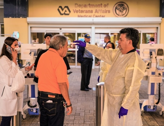 A staffer at the VA Caribbean Healthcare System in San Juan, Puerto Rico, checks the temperature of an incoming visitor during a coronavirus symptoms check on March 19, 2020. (1st Sgt. Rodolfo Armando Barrios Quinones/Army)