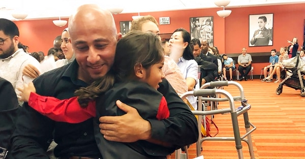 Haeder Al Anbki hugs his son Alasaad, during a naturalization ceremony in Orlando, Fla., Tuesday, July 31, 2018. Al Anbki, a former Iraqi translator and Florida National Guard member, sued a federal agency after he was pulled out of a naturalization ceremony last year without explanation. (Mike Schneider/AP)