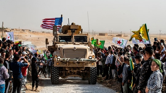 Syrian Kurds gather around a U.S. armored vehicle during a demonstration against Turkish threats next to a U.S.-led international coalition base on the outskirts of Ras al-Ain town in Syria's Hasakeh province near the Turkish border on Sunday Oct. 6, 2019. US forces in Syria started pulling back today from Turkish border areas, opening the way for Ankara's threatened military invasion and heightening fears of a jihadist resurgence (Delil Souleiman/AFP via Getty Images)