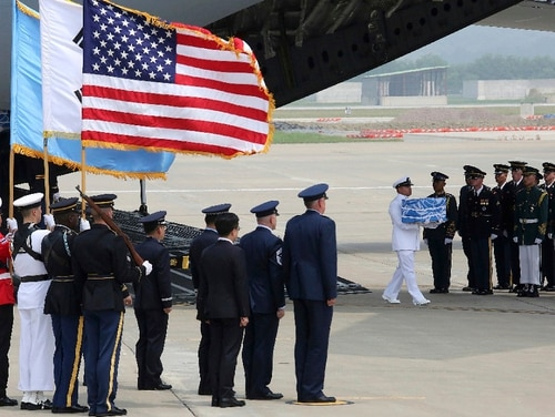 A U.N. honor guard carries a casket containing remains believed to be from American servicemen killed during the 1950-53 Korean War after arriving from North Korea, at Osan Air Base in Pyeongtaek, South Korea, Friday, July 27, 2018. The U.N. Command says the 55 cases of war remains retrieved from North Korea will be honored at a ceremony next Wednesday at a base in South Korea. (Ahn Young-joon/Pool via AP)