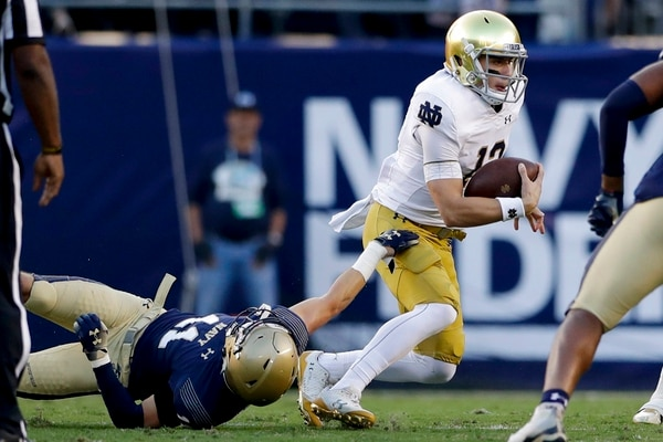 Notre Dame quarterback Ian Book, right, breaks free from Navy linebacker Evan Fochtman, below, during the Saturday game in San Diego. (Gregory Bull/AP)