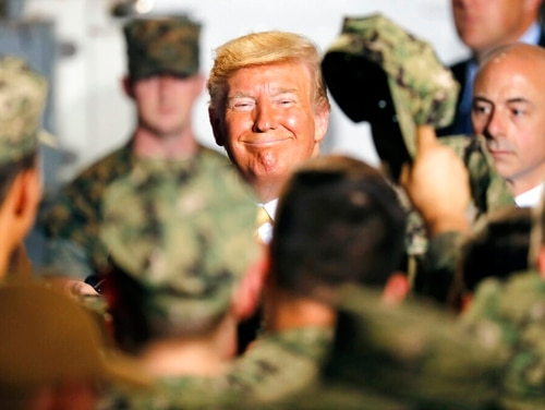 President Donald Trump greets service members aboard the amphibious assault ship Wasp in Yokosuka, Japan, where he addressed them for Memorial Day. (Eugene Hoshiko/AP)