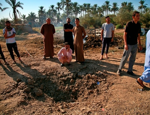 People inspect a crater caused by a deadly Katyusha rocket attack near international airport in Baghdad, Iraq, Tuesday, Sept. 29, 2020. (Khalid Mohammed/AP)