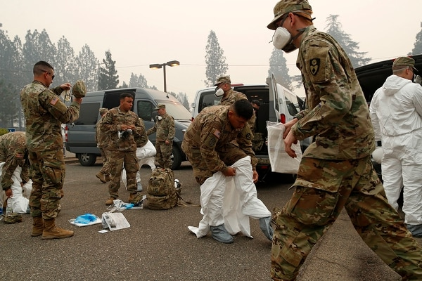 Members of the California Army National Guard don protective suits in preparation to search for human remains at the Camp Fire, Wednesday, Nov. 14, 2018, in Paradise, Calif. (John Locher/AP)
