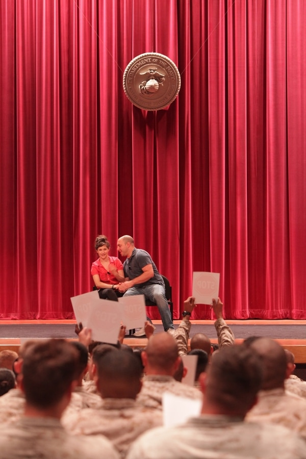 Annie Rex and George Zerante, actors with Catharsis Productions, perform sexual assault training called Sex Signals for Marines at the base theater aboard Camp Pendleton, Calif., Aug. 15. Marines are encouraged to hold up stop signs when they feel a scene displays sexual assault as well as interact with the performers during the show.