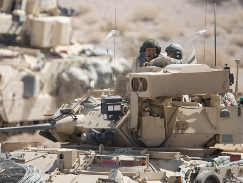 M2A3 Bradley Fighting Vehicle crew discuss an enemy target location while at the National Training Center, Fort Irwin, Calif., Aug. 25, 2015. (Maj. W. Chris Clyne/Army)