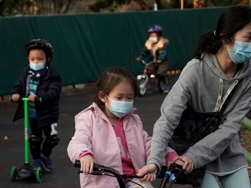 Children wearing masks, play in a park in Hong Kong on Friday. Hong Kong Chief Executive Carrie Lam announced on Friday that all schools will remain closed until March 2, as part of measures to contain the spread of a new virus in the region. (Kin Cheung/AP)