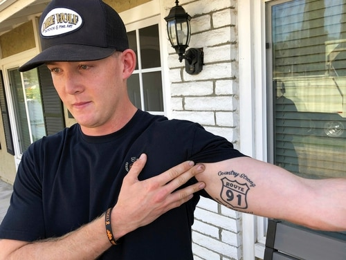 Brendan Kelly speaks with reporters outside his home, as he shows his Route 91 tattoo, Nov. 8 in Thousand Oaks, California. Kelly, a Marine who was at Borderline Bar and Grill on Wednesday night, helped people get out after a gunman opened fire at the establishment. Kelly also survived the Las Vegas Route 91 Harvest Festival shooting in 2017. (Ryan Pearson/AP)
