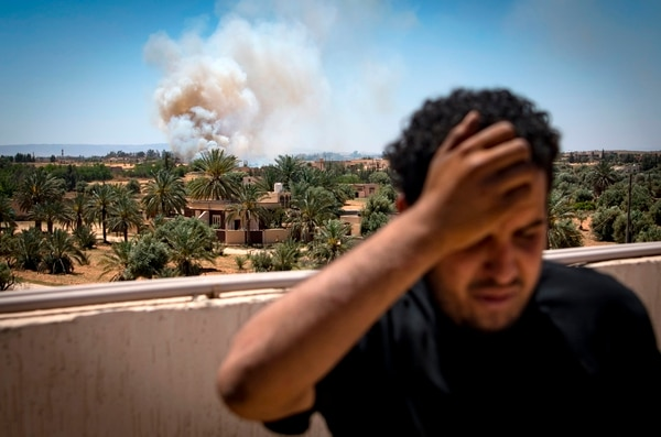 A fighter loyal to the internationally recognized Government of National Accord stands on a rooftop as smoke rises in the distance during clashes with forces loyal to strongman Khalifa Haftar, in Espiaa, about 25 miles south of the Libyan capital Tripoli, on April 29, 2019. (Fadel Senna/AFP via Getty Images)