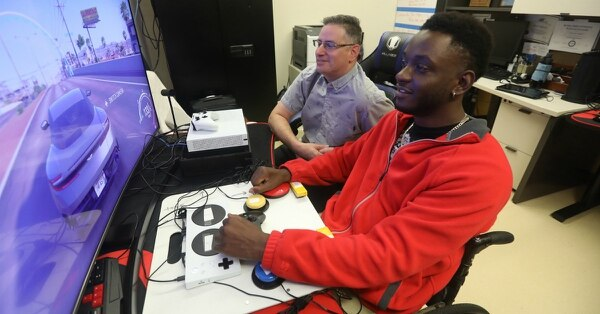 Mike Monthervil, a U.S. Army veteran (front), and Jamie Kaplan, recreation therapist at the James A. Haley Veterans' Hospital in Tampa, Fla., play a video game using an Xbox adaptive controller. (Jeff Young Photography/Microsoft)