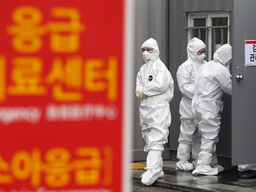 Officials wearing protective attire work to diagnose people with suspected symptoms of the new coronavirus at a hospital in Daegu, South Korea, Wednesday, Feb. 26, 2020. (Kim Hyun-tae/Yonhap via AP)