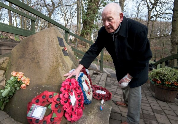 Tony Foulds tends to the memorial honoring 10 U.S. airmen who died in a plane crash in Endcliffe Park, Sheffield, England. Foulds, 82, dreamed of honoring them for decades and finally got his wish. (Rui Vieira/AP)