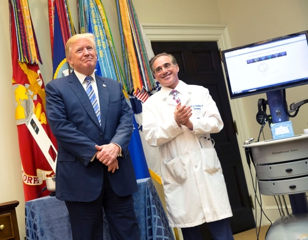 President Donald Trump listens to applause with Veterans Affairs Secretary David Shulkin at a telemedicine demonstration at the White House on Aug. 3, 2017. Shulkin was fired last month before signing a contract to overhaul VA's electronic medical records systems. (Chris Kleponis/Getty Images)