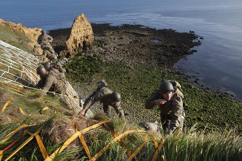Soldiers from the U.S. 75th Ranger Regiment, in period dress, climb the cliff of Pointe-du-Hoc