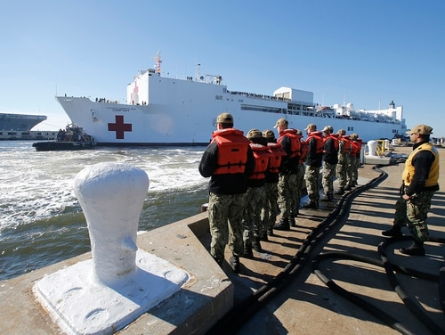 Line handlers wait as the Navy hospital ship USNS Comfort arrives pier side at Naval Station Norfolk, Tuesday, Dec. 18, 2018, in Norfolk , Va., after an 11-week medical support mission to South and Central America. (Steve Helber/AP)