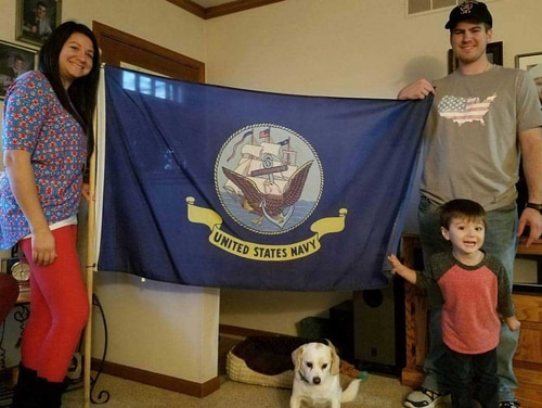 Navy Yeoman 1st Class Eric Driest displays a Navy flag with his wife, Lisa, his son, Peyton, and dog Paisley. Eric and Lisa are poring over the financial details before making a final decision about which retirement system he will choose. At this point, they simply aren't sure. (Courtesy of Eric Driest)