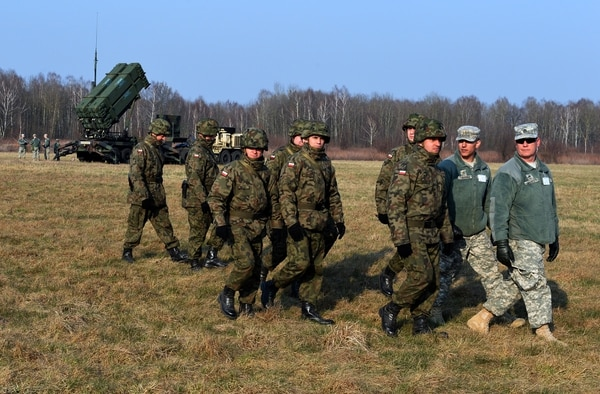 Polish soldiers watch as U.S. troops set up a launching station for the Patriot air and missile defense system at a test range in Sochaczew, Poland, in 2015. (Janek Skarzynski/AFP/Getty Images)