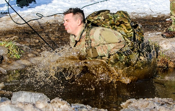 Pfc. Ryan Oliver, a wheeled vehicle mechanic with the 82nd Brigade Engineer Battalion, 2nd Armored Brigade Combat Team, 1st Infantry Division, jumps into a lake during cold-water immersion training with the U.K. 1st Royal Welsh Battalion in Tapa, Estonia on March 7. (Spc. Hubert D. Delany III/Army)