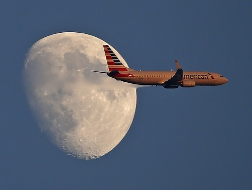 An American Airlines jetliner flies past the moon on Sept. 1, 2017, in Arlington, Texas. (Ron Jenkins/Getty Images)