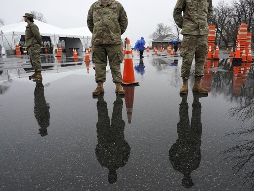 National Guard troops stand by as people wait to be tested for coronavirus (COVID-19) on March 13, 2020, at the state's first drive through COVID-19 mobile testing center at Glen Island Park in New Rochelle, N.Y. (Timothy A. Clary/ AFP via Getty Images)
