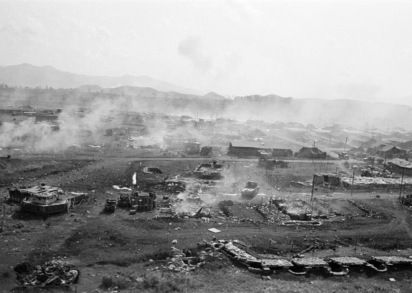 This aerial view shows part of the U.S. Marine outpost and airfield at Khe Sanh with bunkers, ammunition dump and huts smoldering from rocket and mortar attack by elements of North Vietnamese 325 C Division the morning of Jan. 21, 1968. The Khe Sanh Valley area is seven miles east of Laos and 16 miles south of the demilitarized zone. (Dang Van Phuoc/AP)