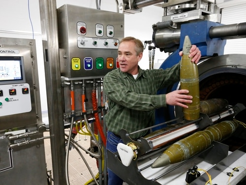 In this file photograph taken Thursday, Jan. 29, 2015, project manager Steve Bird holds an inert 105mm shell as he demonstrates the use of the explosive destruction system used for eliminating leaky or otherwise problematic chemical munitions, inside the Pueblo Chemical Depot, east of Pueblo, in southern Colorado. (Brennan Linsley/AP)
