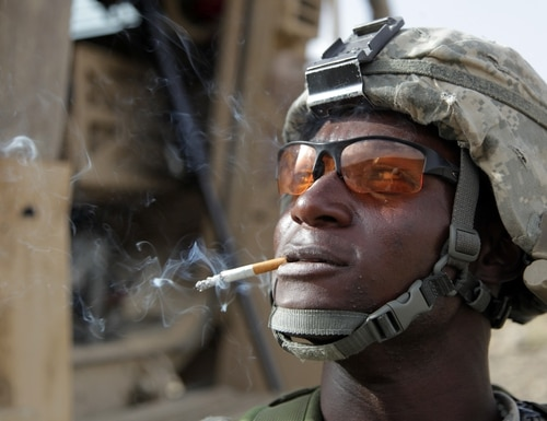 U.S. Army Spc. Olufemi Odueyungbo enjoys a cigarette prior to getting back in his vehicle after a mission in Afghanistan. (Army)