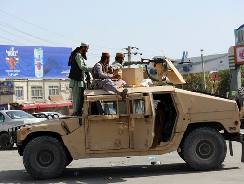 Taliban fighters stand guard in front of the Hamid Karzai International Airport in Kabul, Afghanistan, on Aug. 16. (Rahmat Gul/AP)
